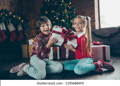 Nice adorable cheerful glad excited small little offspring kids, brother and sister, sitting on floor near fir tree, holding big white box from santa