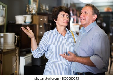 nice adult woman with her husband are buying furniture for home in antique store