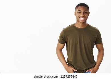 Nice african american guy smiling at camera while standing in casual pose in hucky t-shirt with hands in pockets looking friendly and self-assured making new friends, meeting coworker at new job