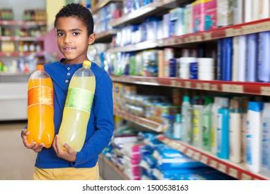 Nice African American preteen boy standing with bottles of soda drinks in supermarket
