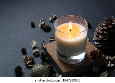 nice aromatic scented candle glass is lighting on the wooden holder on black wooden table with dried flowers , herbs and spices in the living room during Christmas new year party with happy family