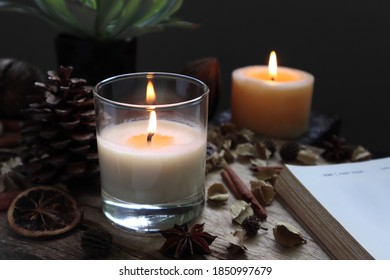 nice aromatic scented candle glass is lighting on the wooden holder on black wooden table with dried flowers , herbs and spices pinecone in the living room during Christmas new year party happy family - Shutterstock ID 1850997679
