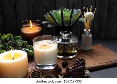 nice aromatic scented candle glass and reed diffusers  lighting on wooden holder on black wooden table with dried potpourri , herbs and spices pinecone in living room during Christmas new year party - Shutterstock ID 1857197338
