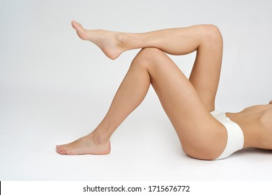 Nice attractive adorable lovely serious calm thin skinny brunette girl clean clear smooth healthy skin isolated over light gray background. Hair removal advertisement. Lying on backs, shows legs.