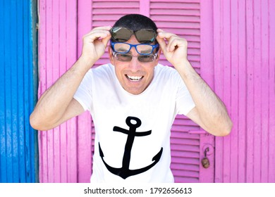 Nice attractive funny happy guy wear sailor shirt feel cool with three pears of specs enjoy the summer on the beach over a bright vivid vibrant pink blue color background