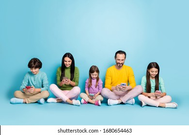 Nice attractive lovely charming focused cheerful cheery big full family pre-teen kids sitting in lotus pose browsing web isolated on bright vivid shine vibrant blue color background