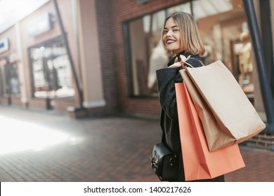 Nice attractive young woman pose on camera and smile. Loook back and hold shopping bags. Stand in mall alone. Model with short haircut