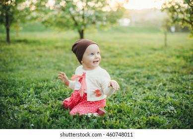 Nice baby girl in green meadow
