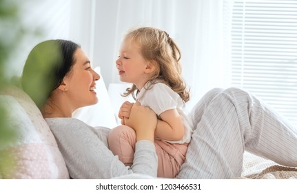A nice baby girl and her mother enjoy sunny morning. Good time at home.