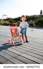 A nice baby girl model with toy stroller on a wooden promenade.