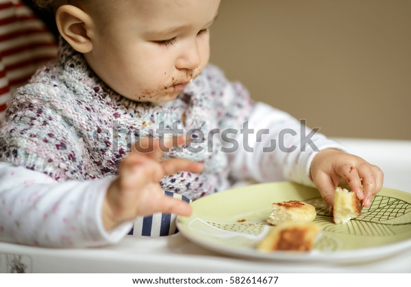 The nice baby with messy face sits on a high chair and eating cheese cakes. Feeding baby at home. The one-year-old child learns to eat by himself.