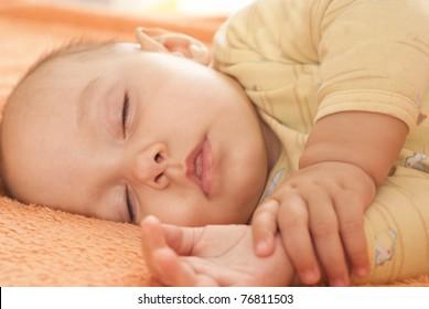 nice baby sleeping on the orange towel