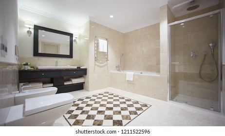 Nice bathroom in a modern style with gray tiled walls. There is a white bath with a glass partition, shower, mirrors, light sink, toilet and a bidet, luminous lamps