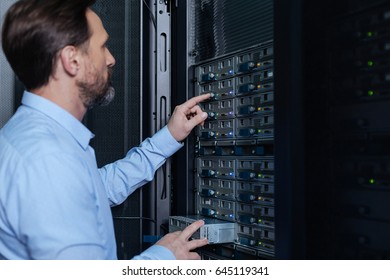 Nice bearded man setting up the network server