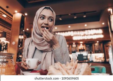 nice beautiful Arab girl in hijab dines in oriental cafe, tasty food