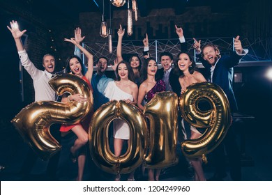 Nice beautiful attractive adorable pretty winsome charming cheerful ecstatic ladies and handsome gentlemen, chill out at fashionable night club, raising hands up, holding big 2019 symbol