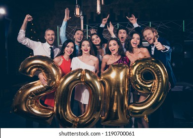 Nice beautiful attractive pretty winsome charming cheerful glad ladies and handsome gentlemen, chill out at fashionable night club, raising hands up, holding shiny bright 2019 symbol