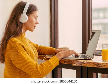 Nice beautiful female with blonde long hair working on laptop sitting at home. Online shoping, alternative office freelance, gig economy, digital nomad