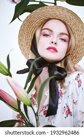 Nice beautiful girl in a straw hat and a summer blouse posing with lily flowers on a white background. Inspiration of spring and summer. Light fresh makeup in pink colors. Perfume and cosmetics.