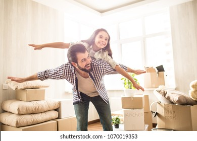 Nice and beautiful picture of father and daughter spending time together. Girl is lying on her dad's back and pretending she is flying. Her dad is doing the same thing. Both of them are happy.