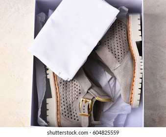 Nice beautiful womans fashionable suede leather grey boots with white sole in shopping box with cloth on beige background