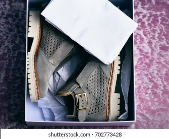 Nice beautiful womans fashionable suede leather grey boots with white sole in shopping box with cloth on textured pink background