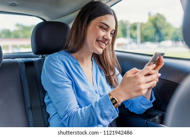 nice beautiful young woman smile and use mobile phone touching the screen inside the car while travel. modern concept of search hings and contact friends when you are away. daily use of smartphone