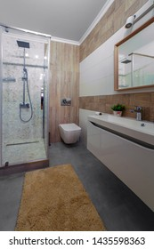 Nice beige bathroom with glass shower, and washing machine.