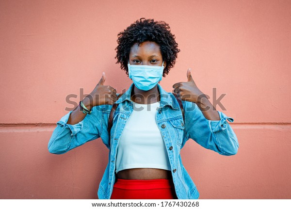 nice black girl, smiling with the eyes and wearing protective and medical mask, making the gesture of thumbs up, positive and optimism, over pastel coral pink background, vignetting effect