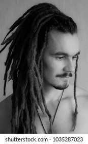 A nice black and white portrait of a young man wearing long dreadlocks