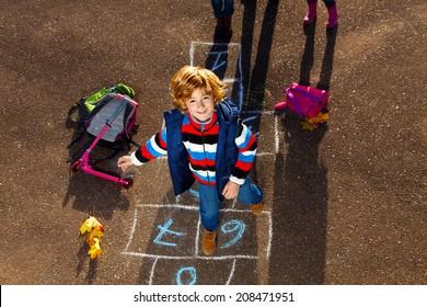 Buen chico rubio saltando sobre un partido de fútbol sala tras colegio con bolsas y scooter tendidos cerca