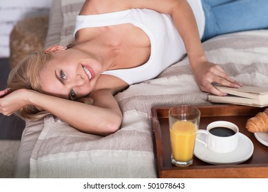 Nice blond woman lying on bed with book