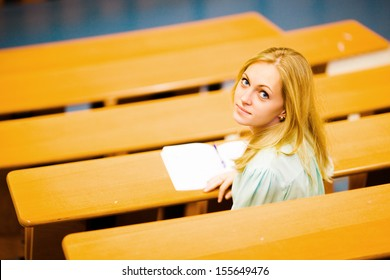 Nice blonde blue-eyed student girl in auditorium writing down turned around