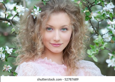 nice blonde with curly hair posing in orchard