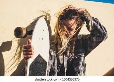 nice blonde woman enjoy the freedom with wind in her hair and skateboard to move and feel the roads and the travel. youth concept independence