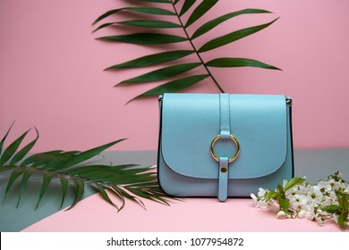 Nice blue leather female bag on the pink background in the studio. There are green branches and white flowers next to it. Closeup. Horizontal.