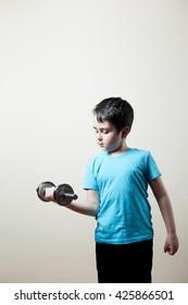 nice boy lifting dumbbell on biceps