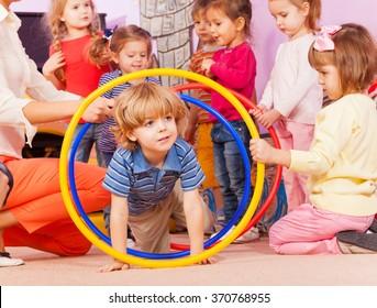 Nice boy play with hoops in kindergarten goup