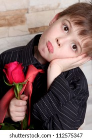 the nice boy with a red rose in a hand