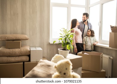 Nice and bright apartment. Young and happy family has just moving into it. There are boxes with their stuff everywhere. The family is standing close to the windows and talkin with each other.