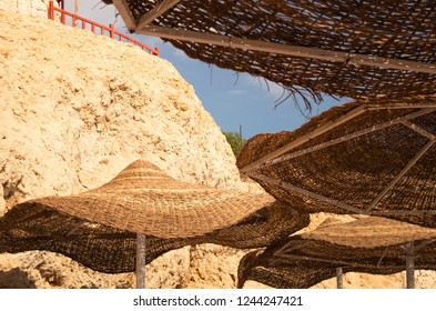 Nice bright picture with a several straw sunshades at the beach. Warm and hot weather outdoors. Some of the sunshades are close-up.