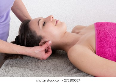 Nice brunette on massage table, getting acupuncture point on her ear
