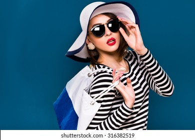 Nice brunette woman, with short haircut, wearing in striped blouse, black sunglasses and white hat, is posing with white and blue bag, on blue background, in studio, waist up