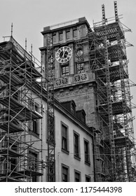 Nice building with a tower and a tower clock on a top. Scaffold. Building repair. Restoration. Technical University of Munich. Black White photography. Germany, Munich – November 18, 2017