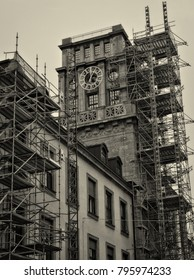 Nice building with a tower and a tower clock on a top. Scaffold. Building repair. Restoration. Technical University of Munich. Black White photography. Germany, Munich - November 18, 2017