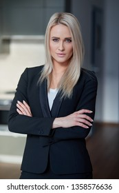 Nice and calm blond, middle age business woman standing at her office. Looking at camera. She wearing black formal suit and white tshirt.