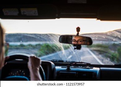 nice caucasian adult lady drive the car with dirty glass. long way road traveling to the sunset in front. outdoor nature and mountains. looking the back mirror to check the traffic