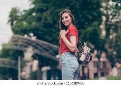 Nice charming attractive cute young smiling girl with bag bagpack outdoors, wearing casual red t-shirt and jeans, walking strolling