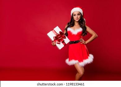 Nice charming pretty adorable lovable positive sweet gorgeous curly-haired lady in hat and fluffy dress, keeping, holding, showing gift box, isolated over bright vivid red background