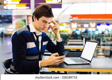 Nice cheerful handsome guy sitting at the table and reads a message on his phone while working on the computer. Business freelance man smiling and sitting at table with a laptop in airport cafe.